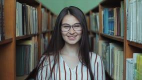 Porträt des jungen schönen Mädchens in der Bibliothek stock footage