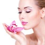 Porträt des jungen schönen Mädchens mit Blume nahe dem Gesicht Stockfotos