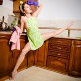 Porträt des jungen schönen super flexiblen Frau Pinupmädchens in den purpurroten Handschuhen an der Küche mit Beinspalte Lizenzfreie Stockfotografie
