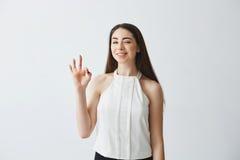 Porträt des jungen schönen zarten Mädchens, welches die Kamera blinzelt lächelndes über weißem Hintergrund o.k. darstellen betrac Stockfotos