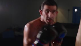 Porträt des jungen schulterfreien männlichen Boxers, der Kamera betrachtet und mit Schatten kämpft stock video