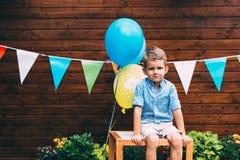 Porträt des Jungen sitzend auf Tabelle an der Geburtstagsfeier Stockbild