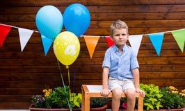 Porträt des Jungen sitzend auf Tabelle an der Geburtstagsfeier Lizenzfreie Stockbilder