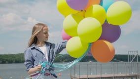 Porträt des jungen spielerischen Mädchens mit bunten Ballonen in einem Teich stock video footage