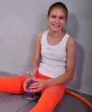 Porträt des jungen sportiven jugendlich Mädchens mit einer Flasche Trinkwasser Lizenzfreies Stockfoto