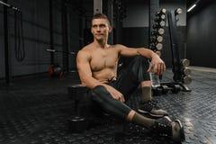 Porträt des jungen sportlichen Mannes mit Flaschenrest in der Turnhalle nach Training lizenzfreie stockfotos