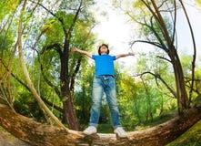 Porträt des Jungen stehend auf gefallenem Baumstamm Lizenzfreie Stockfotos