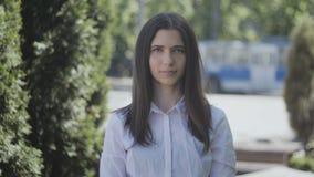Porträt des jungen Studentinnachmittages in einer Stadtstraße, welche die Kamera betrachtet stock video footage