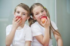 Porträt des Jungen und des Mädchens in den weißen T-Shirts Äpfel essend Stockfotos