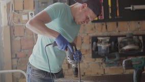 Porträt des jungen Vorlageningenieurs gerichtet auf die Bohrung eines Lochs mit Werkzeug auf dem Hintergrund einer kleinen Werkst stock video