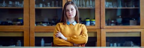 Porträt des jungen weiblichen Studenten im Chemieunterricht, sitzend hinter dem Schreibtisch mit den gekreuzten Armen lizenzfreie stockbilder