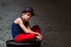 Porträt des kühlen jungen Hip-Hop-Jungen im blauen Hut und roten in den Hosen, die auf schwarzem Fass sitzen Lizenzfreie Stockfotografie