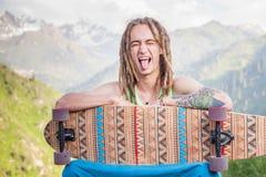 Porträt des kühlen, lustigen gutaussehenden Mannes mit Skateboard am Berg Lizenzfreie Stockfotos