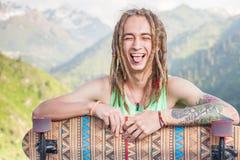 Porträt des kühlen, lustigen gutaussehenden Mannes mit Skateboard am Berg Stockfoto