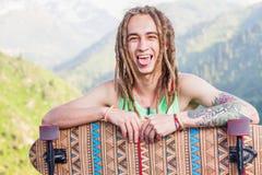 Porträt des kühlen, lustigen gutaussehenden Mannes mit Skateboard am Berg Lizenzfreie Stockfotografie