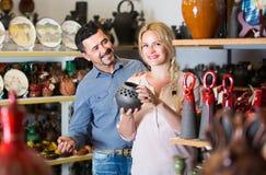 Porträt des kaufenden keramischen Geräts des Mannes und der Frau in der Butike Stockfotos