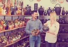 Porträt des kaufenden keramischen Geräts des Mannes und der Frau in der Butike Stockbild