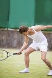 Porträt des kaukasischen gutaussehenden Mannes in der Tennis-Ausstattung, die mit aufwirft Lizenzfreies Stockbild