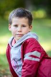 Porträt des kaukasischen Jungen mit sechs Jährigen in der roten Jacke Stockfoto