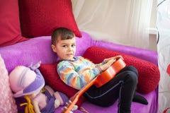 Porträt des kaukasischen kleinen reizend Jungen mit einer Spielzeuggitarre im selektiven Fokus stockfotografie