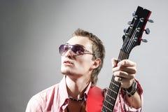 Porträt des kaukasischen männlichen Gitarristen Playing die Gitarre und der Blick Stockfoto