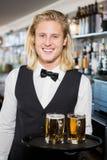 Porträt des Kellners Behälter mit dem Bierkrug halten Stockfotografie