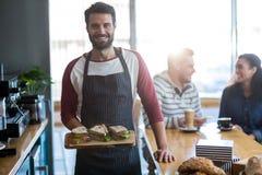 Porträt des Kellners ein Sandwich auf hackendem Brett halten Stockfotografie