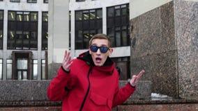Porträt des Kerls in der roten Jacke und in der Sonnenbrille, die nahe bei Granitsäulen klopft stock video
