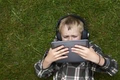 Porträt des Kinderblonden Jungen, der mit einem digitalen Tablet-Computer draußen liegt auf Gras spielt Lizenzfreies Stockfoto