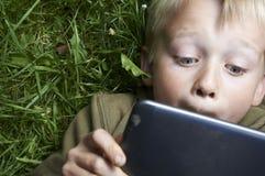 Porträt des Kinderblonden Jungen, der mit einer digitalen Tablette spielt Stockfotos