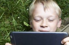 Porträt des Kinderblonden Jungen, der mit einer digitalen Tablette spielt Lizenzfreies Stockbild