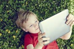 Porträt des Kinderblonden Jungen, der mit einer digitalen Tablette spielt Lizenzfreie Stockbilder