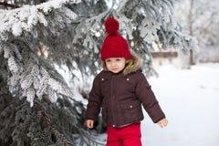 Porträt des Kindes in der braunen Jacke und in rotem Strickmütze- und Rotem tr Stockfoto