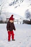 Porträt des Kindes in der braunen Jacke und in rotem Strickmütze- und Rotem tr Stockfotografie