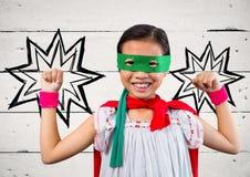 Porträt des Kindes im roten Kap und grünen in der Maske, die mit der Faust steht Lizenzfreies Stockfoto