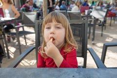 Porträt des Kindes sitzend in der Außenstange, die Käsehauch isst Stockfotografie