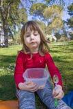 Porträt des Kindes Teigwaren im Park essend Lizenzfreies Stockfoto