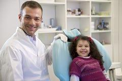 Porträt des Kindes und des Zahnarztes im zahnmedizinischen Studio, camer betrachtend Lizenzfreie Stockbilder