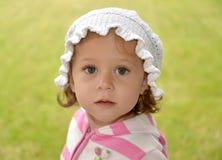 Porträt des kleinen überraschten Mädchens auf den weißen Panamaer an auf einem grünen Hintergrund Lizenzfreie Stockbilder