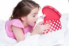 Porträt des kleinen überraschten Mädchens mit einem Geschenk. Stockfoto
