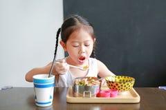 Porträt des kleinen asiatischen Kindermädchens, das am Morgen frühstückt stockfotos