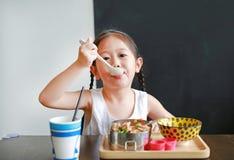 Porträt des kleinen asiatischen Kindermädchens, das am Morgen frühstückt lizenzfreies stockbild