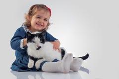 Porträt des kleinen Babys ihre flaumige Katze auf weißem BAC halten Lizenzfreies Stockbild