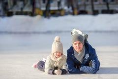 Porträt des kleinen entzückenden Mädchens und des jungen Vatereislaufs Lizenzfreies Stockbild