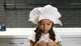 Porträt des kleinen hübschen Mädchens im Chefhut, der mit Teig, Kinderkoch in der wirklichen Küche spielt 4K stock video