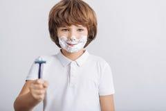 Porträt des kleinen Jungen aufwerfend mit Rasiermesser Stockbild