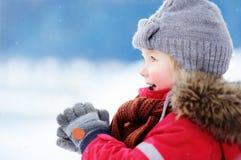 Porträt des kleinen Jungen in der roten Winterkleidung, die Spaß mit Schnee hat Stockfotografie