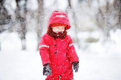 Porträt des kleinen Jungen in der roten Winterkleidung, die Spaß mit Schnee während der Schneefälle hat Stockbild