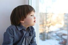 Porträt des kleinen Jungen sitzt auf Schwelle und schaut aus Fenster in w heraus Stockbilder