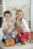 Porträt des kleinen Jungen und des Mädchens mit Schale backt zusammen Stockbild